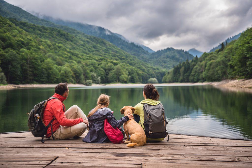 Famille et leur chien assis au bord d'un lac ayant souscrit à la protection juridique.